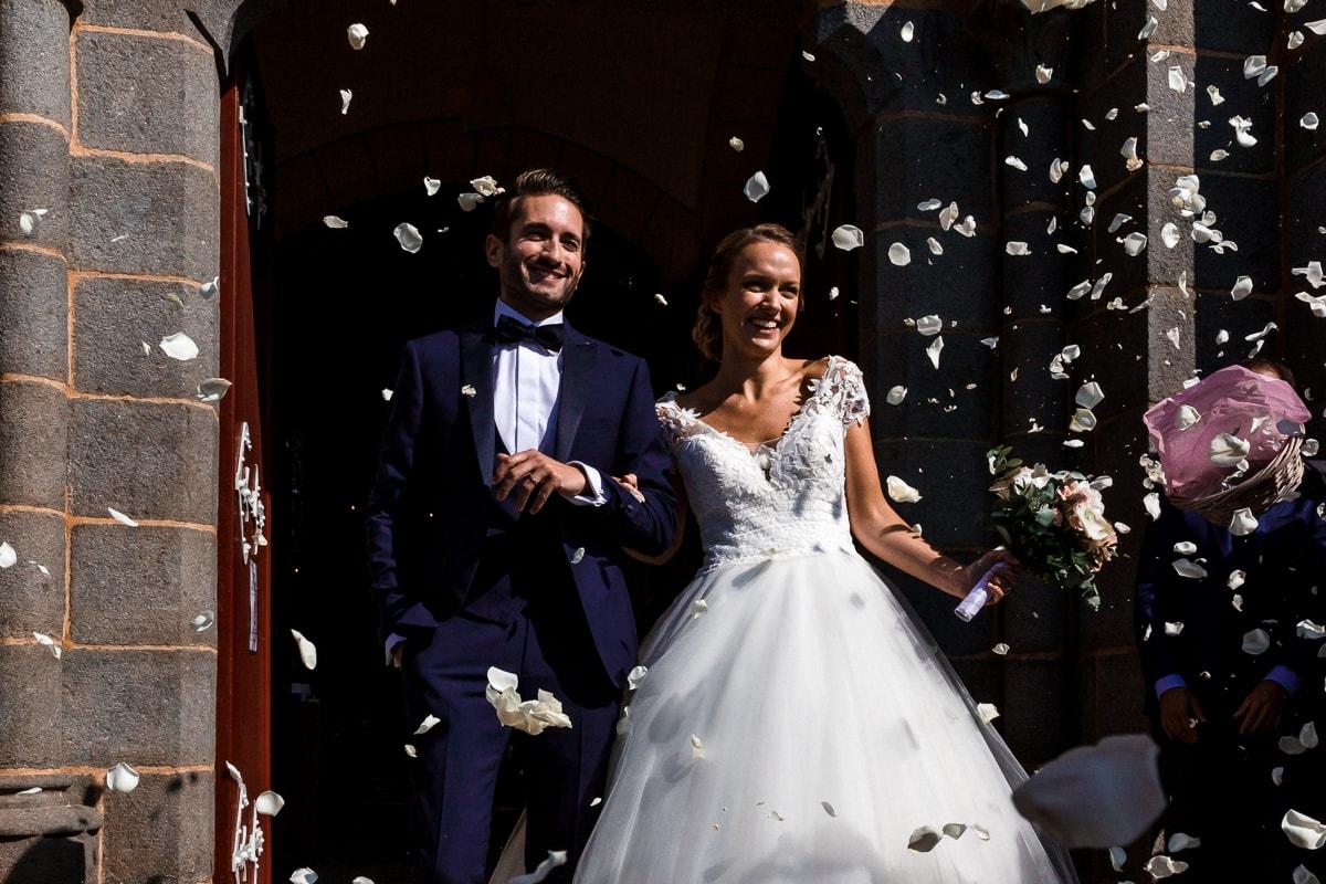 Reportage de mariage. sortie de l'église avec pétales de roses.