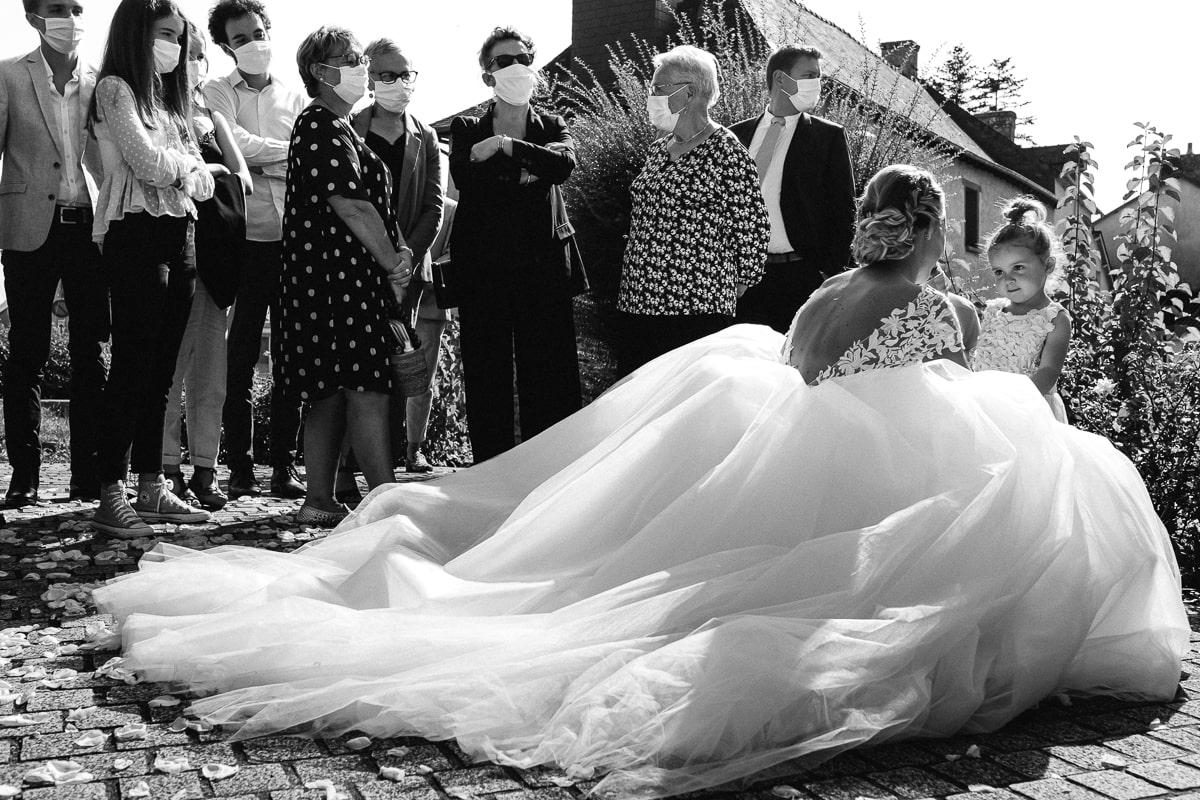 la mariée et sa demoiselle d'honneur. reportage de mariage 2020 avec masques à la sortie de l'église.