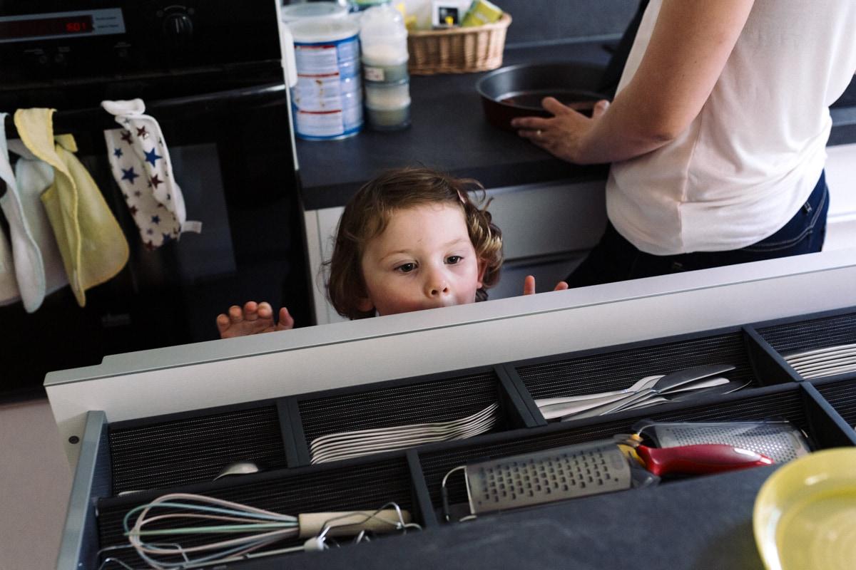 reportage à la maison photo de famille à Rueil Malmaison (92) petit fille curieuse dans la cuisine
