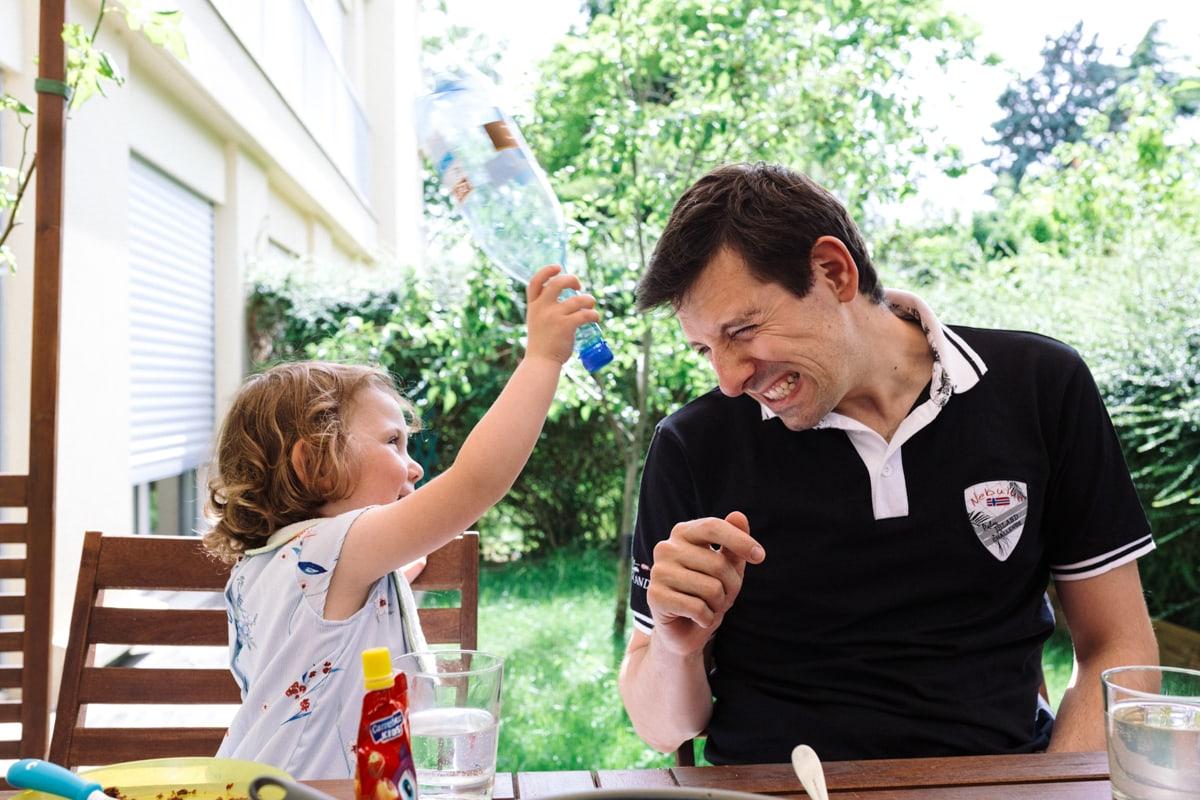 reportage à la maison photo de famille à Rueil Malmaison (92) petite fille tape papa sur la tete avec une bouteille en plastique