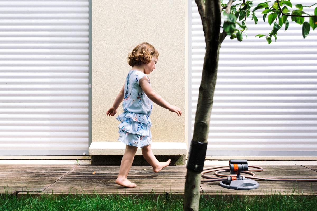 reportage à la maison photo de famille à Rueil Malmaison (92) petite fille qui marche sur la terrasse