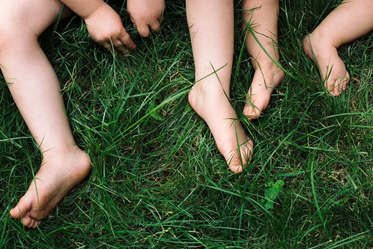 reportage à la maison photo de famille à Rueil Malmaison (92) pieds et mains dans l'herbe