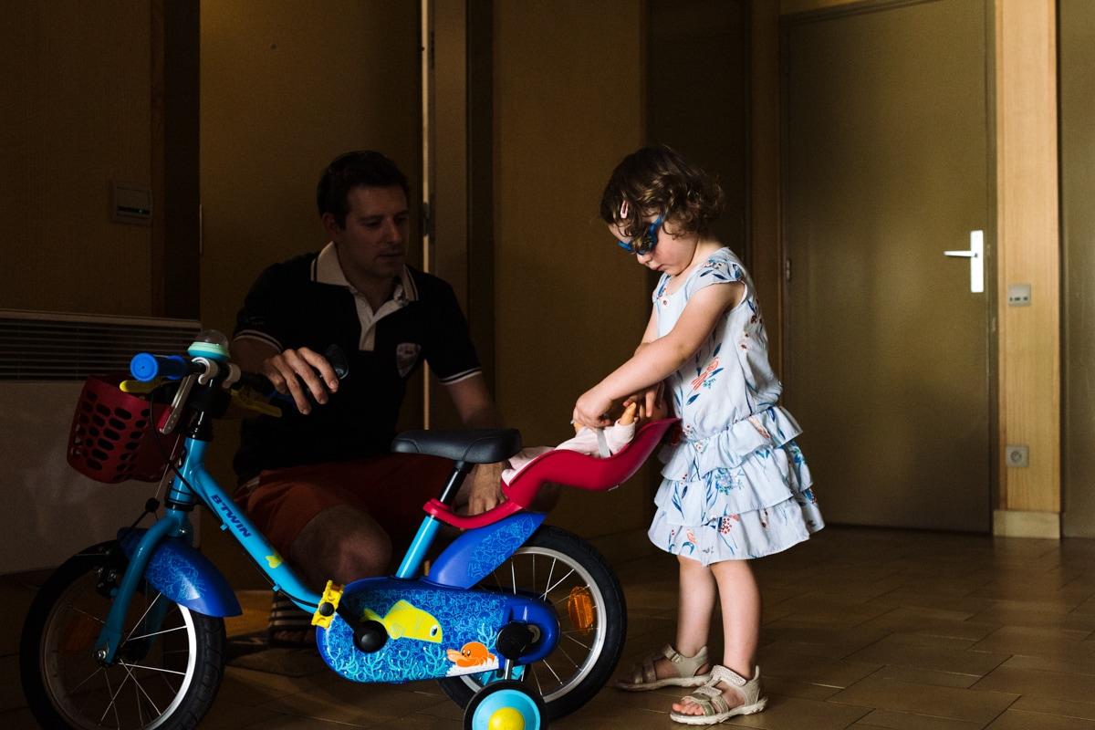 reportage à la maison photo de famille à Rueil Malmaison (92) préparation du vélo avec papa