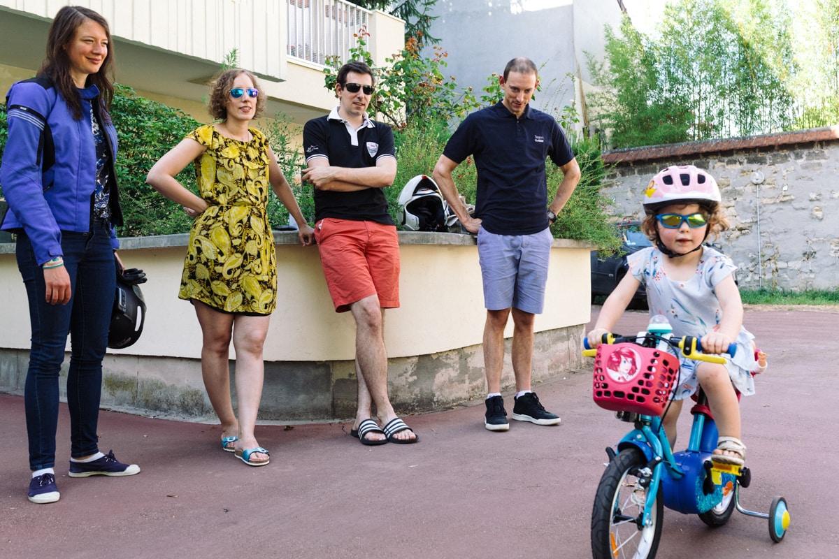 reportage à la maison photo de famille à Rueil Malmaison (92) petite fille a vélo sous le regard des adultes