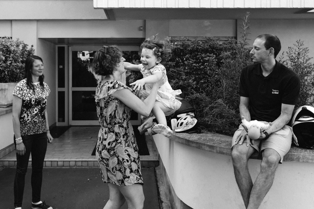 reportage à la maison photo de famille à Rueil Malmaison (92) sauter dans les bras de maman devant tata et tonton