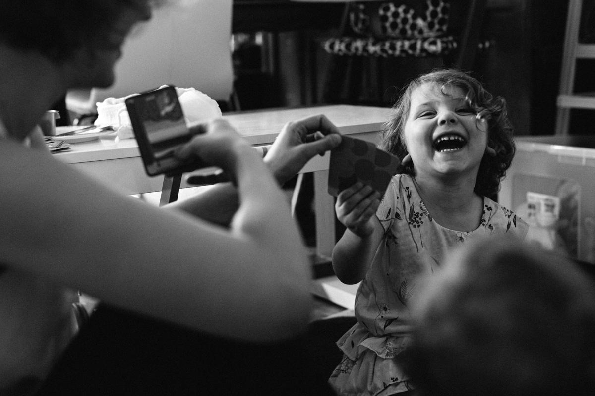 reportage à la maison photo de famille à Rueil Malmaison (92) rire en jouant aux cartes