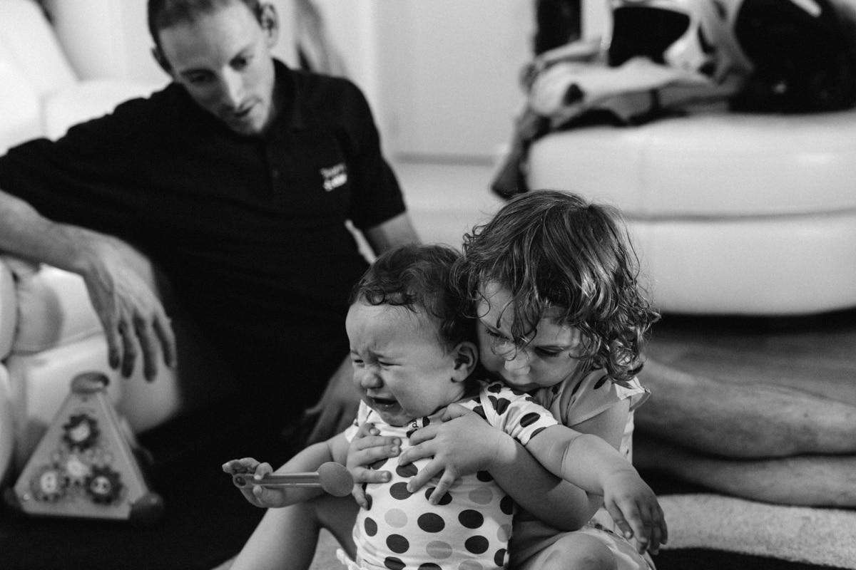 reportage à la maison photo de famille à Rueil Malmaison (92) bébé pleure et grand sœur caline