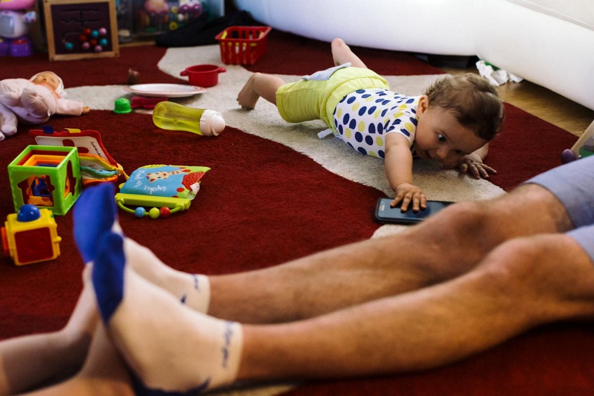 reportage à la maison photo de famille à Rueil Malmaison (92) bébé qui attrape un téléphone portable