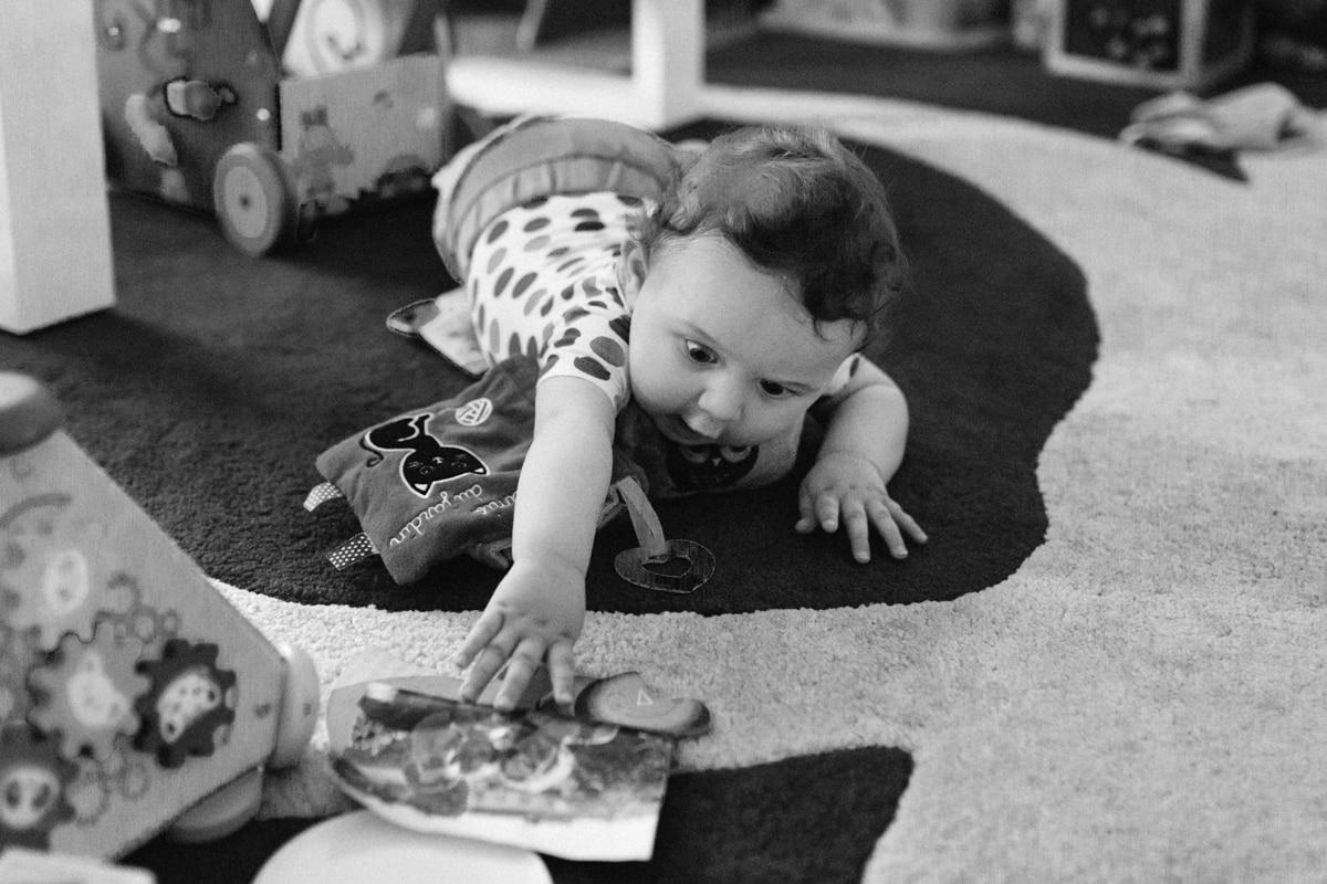 reportage à la maison photo de famille à Rueil Malmaison (92) bébé attrape une photo