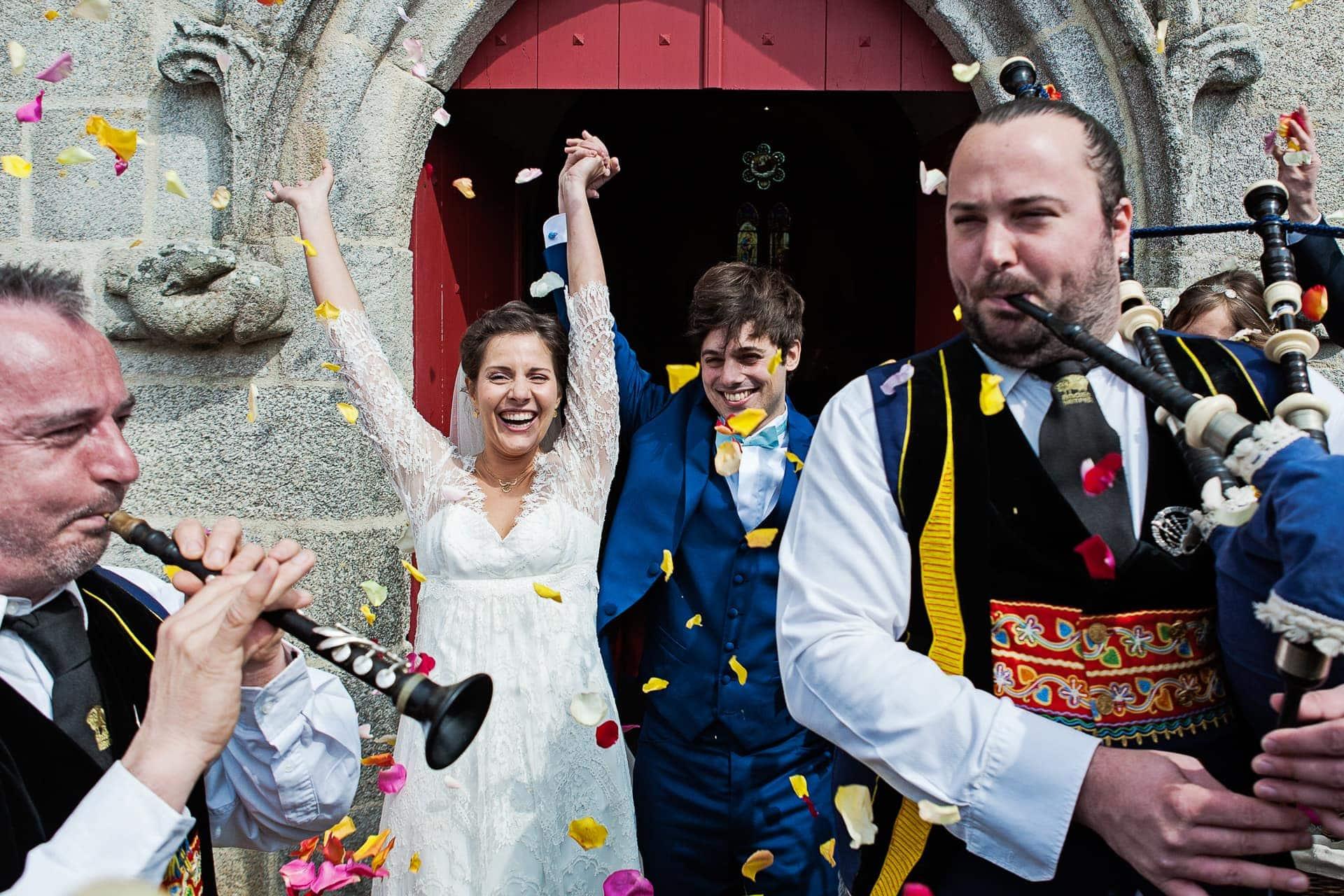 Sortie de l'église sous les confettis avec des sonneurs au premier plan à l'église de Benodet par Ernestine et sa famille photographe de mariage à l'approche reportage