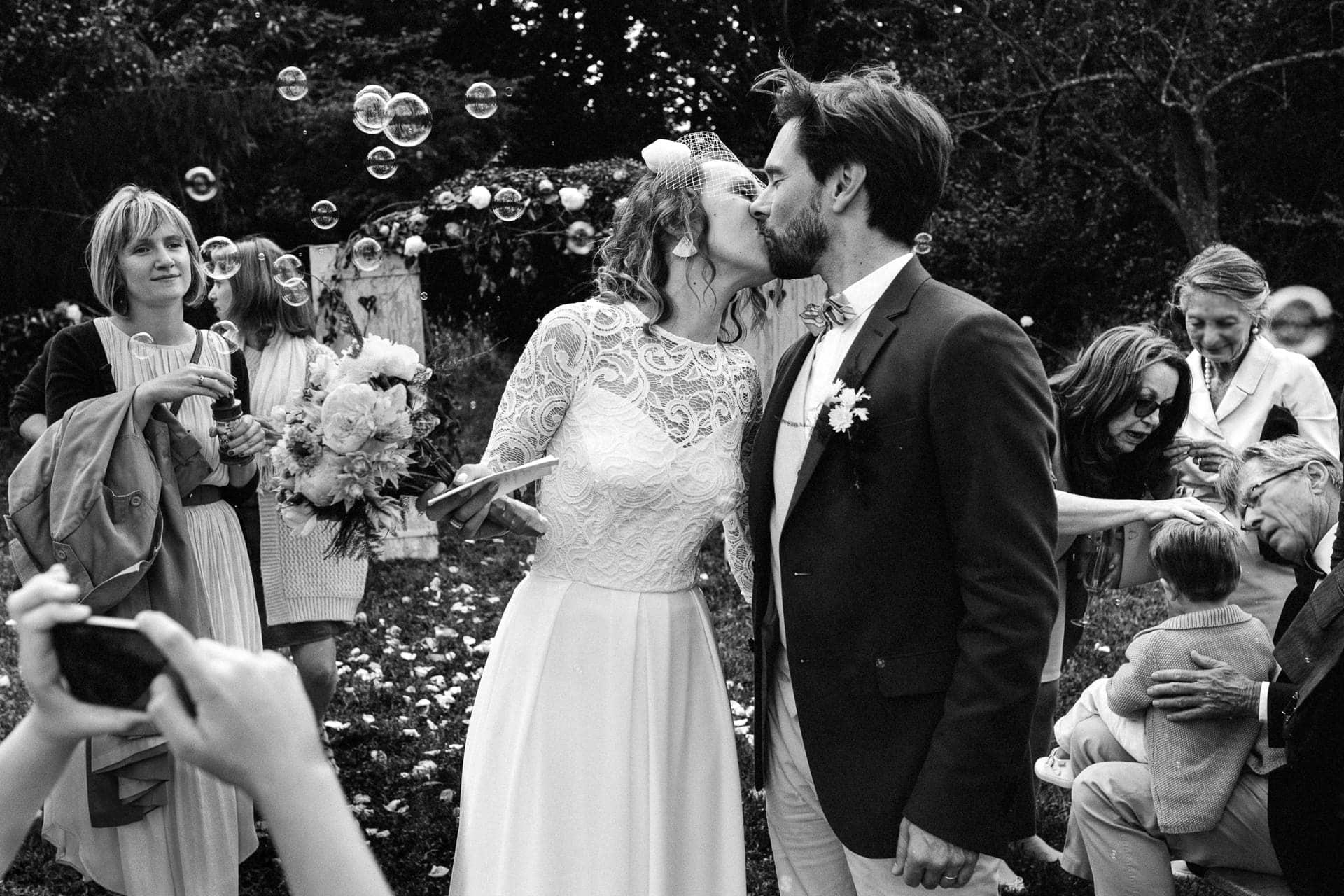 Le baiser des mariés à la fin d'une cérémonie laïque en plein air par Ernestine et sa famille photographe de mariage à l'approche reportage