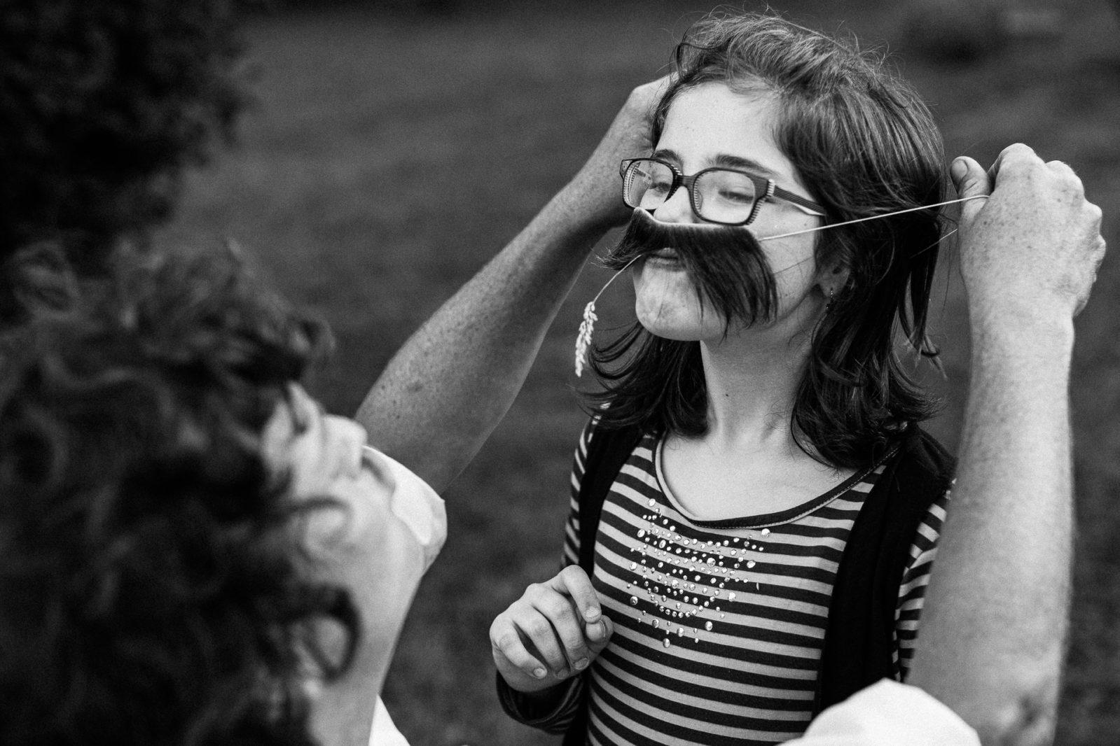 photo d'une enfant avec une fausse moustache Ernestine et sa famille photographe de mariage à l'approche reportageErnestine et sa famille photographe de mariage à l'approche reportage
