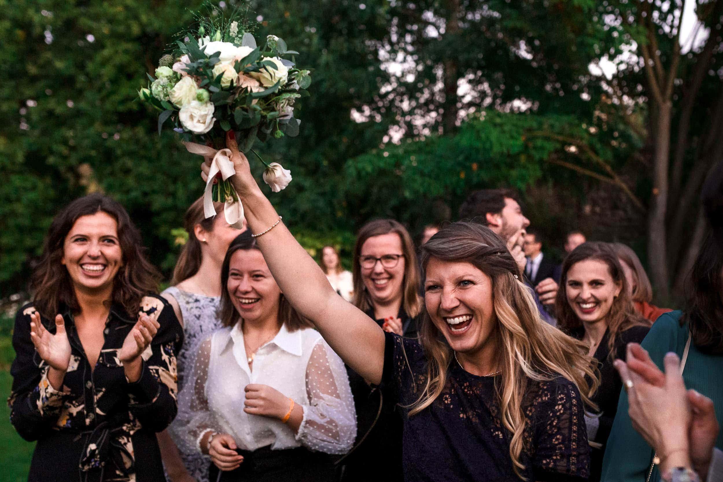 Une invitée attrape le bouquet de la mariée - reportage de mariage au Domaine de Verderonne par Ernestine et sa famille, Marine Poron
