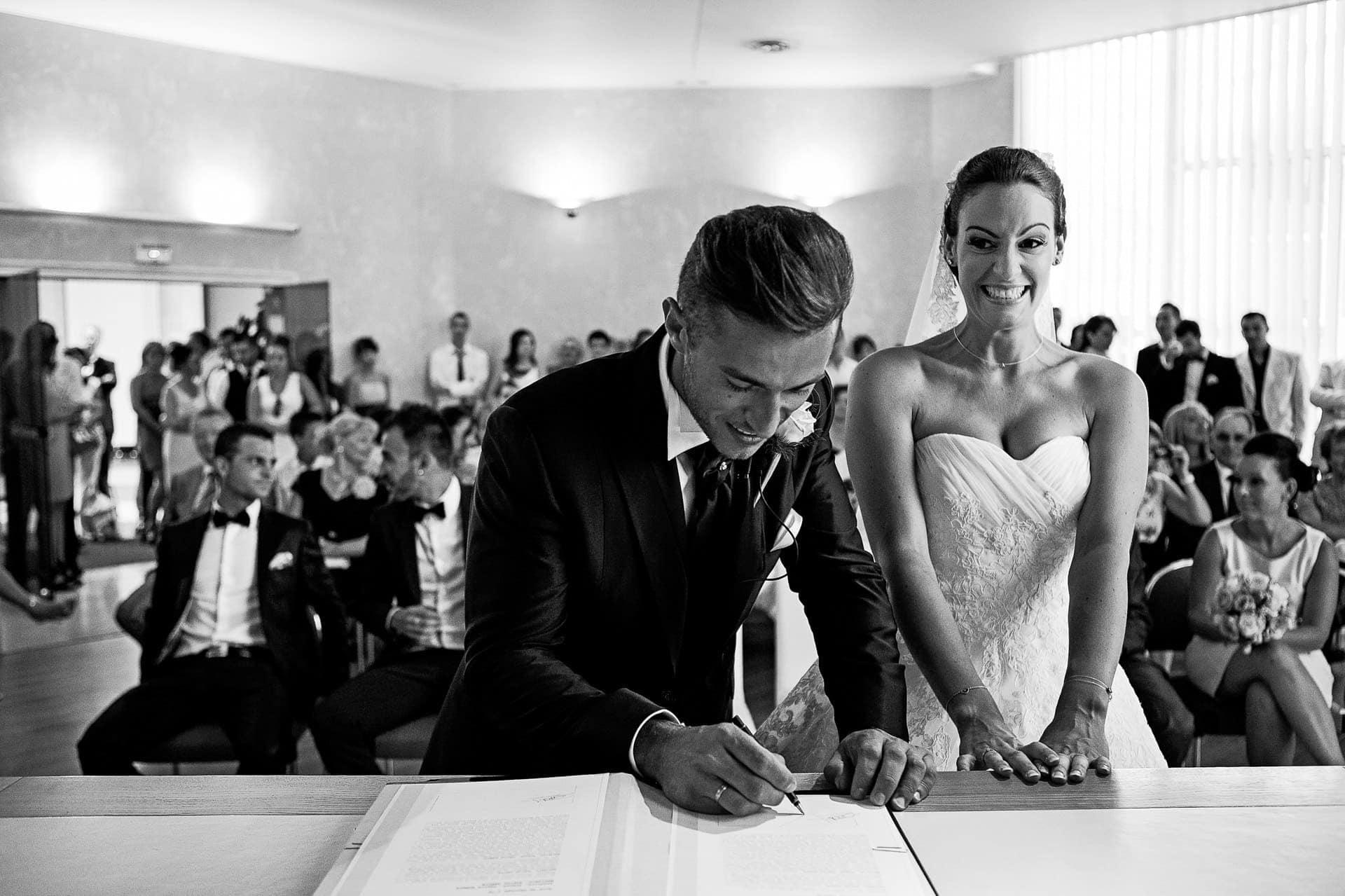 signature des mariés par Photo des mains des mariés pendant la cérémonie laïque . Ernestine et sa famille photographe de mariage à l'approche reportage