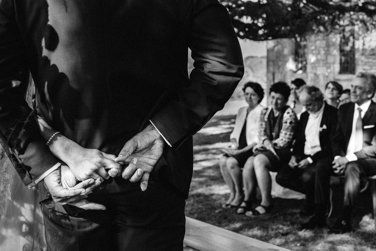 Photo des mains des mariés pendant la cérémonie laïque . Ernestine et sa famille photographe de mariage à l'approche reportage