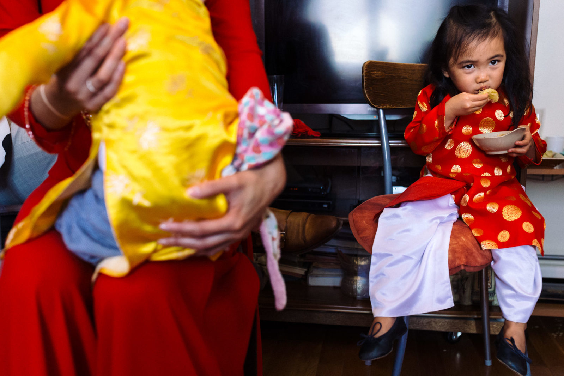 petite fille mangeant des crèpes chinoises Ernestine et sa famille photographe de mariage à l'approche reportage
