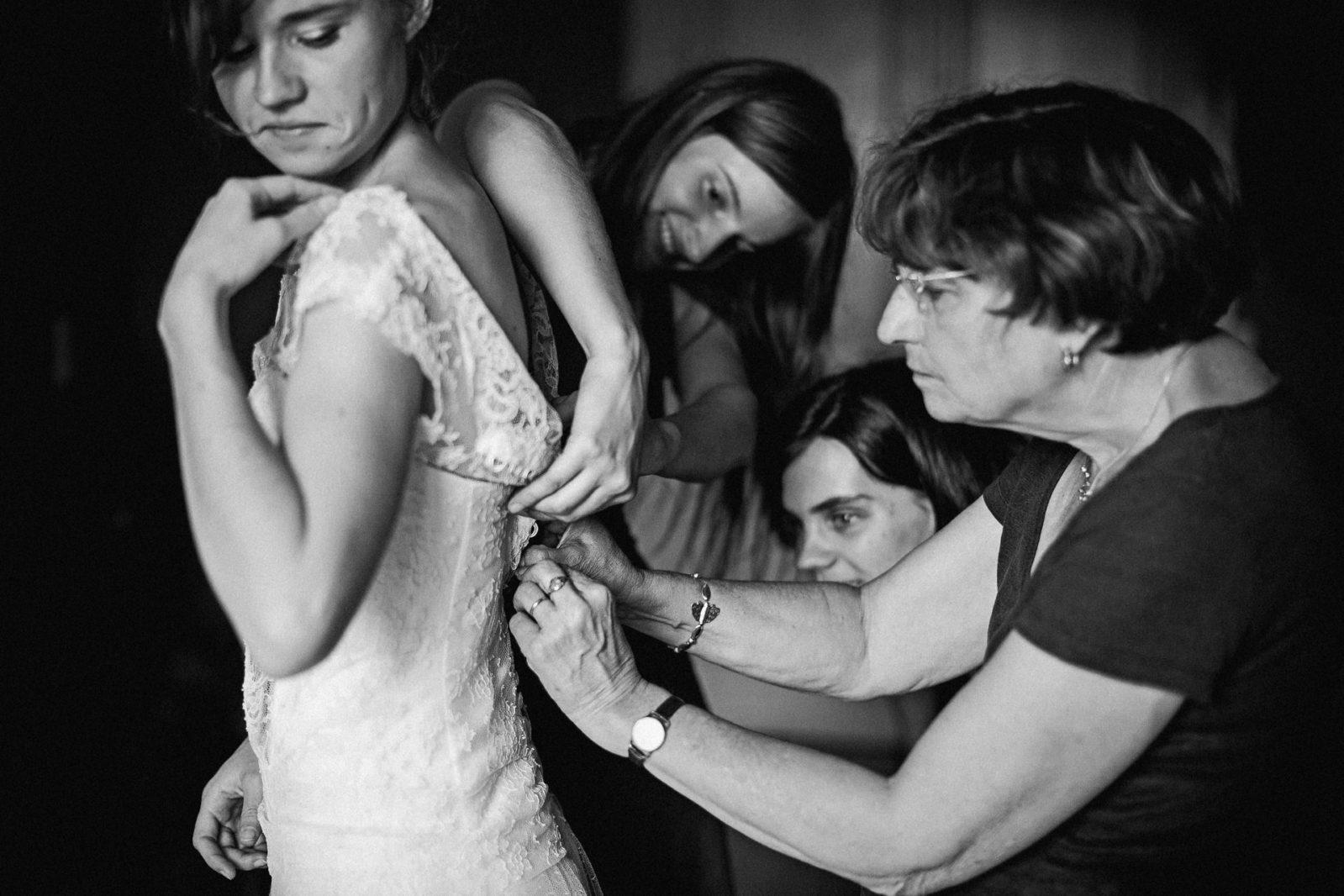 habillage de la mariée par sa mère et ses sœurs à St jean de Luz Ernestine et sa famille photographe de mariage à l'approche reportage