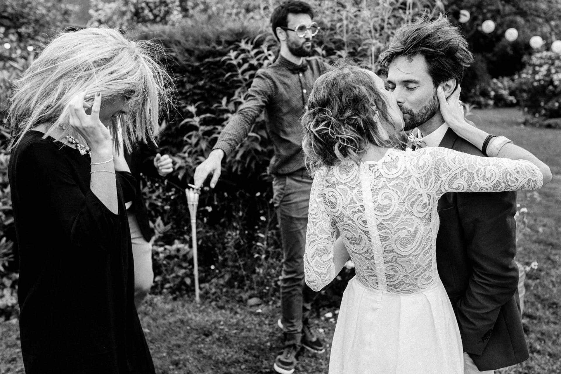les mariés s'embrassent les cheveux au vent Ernestine et sa famille photographe de mariage à l'approche reportage