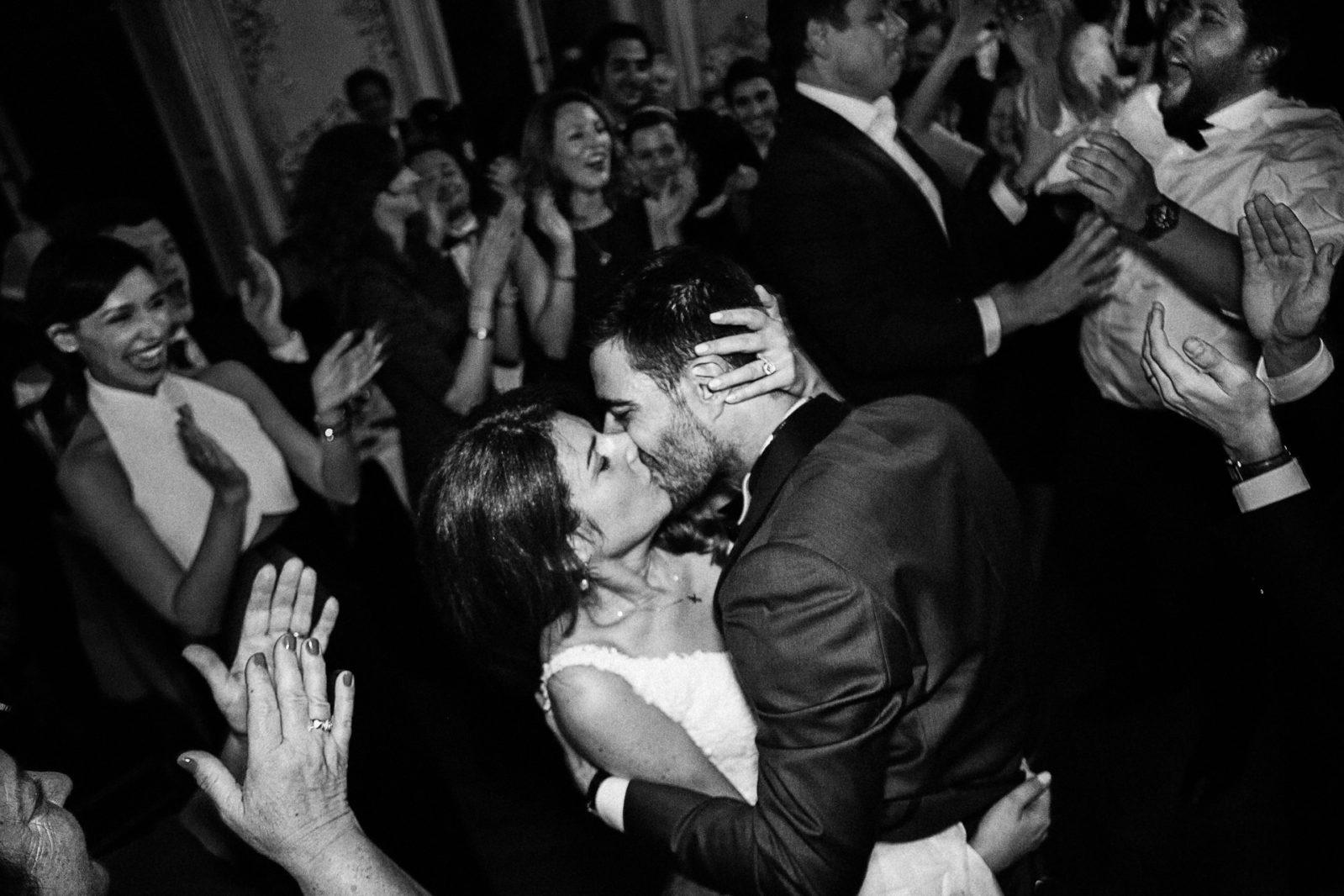 Les mariés s'embrassent au Cercle France Amériques par Ernestine et sa famille photographe de mariage à l'approche reportage
