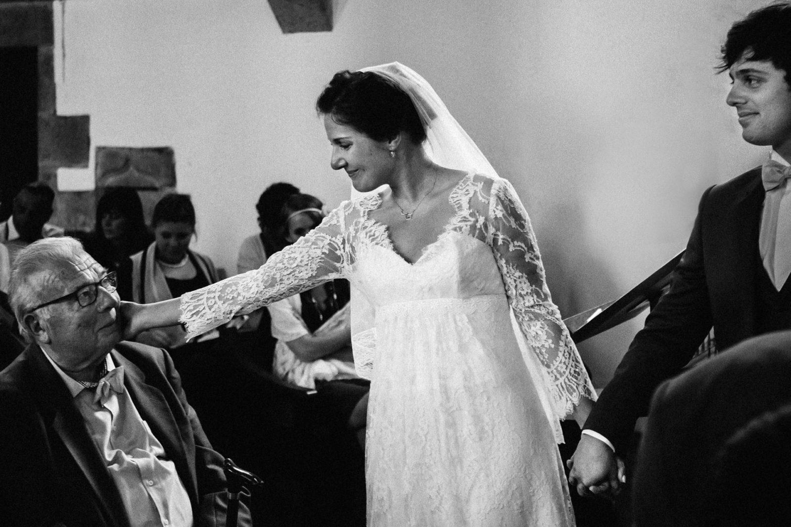 la mariée caresse la joue de son grand père Ernestine et sa famille photographe de mariage à l'approche reportage