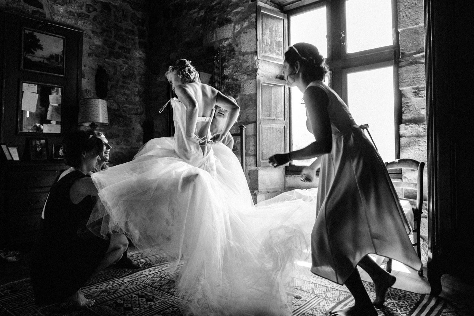 habillage de la mariée Détail de la robe de mariée par Ernestine et sa famille photographe de mariage à l'approche reportage