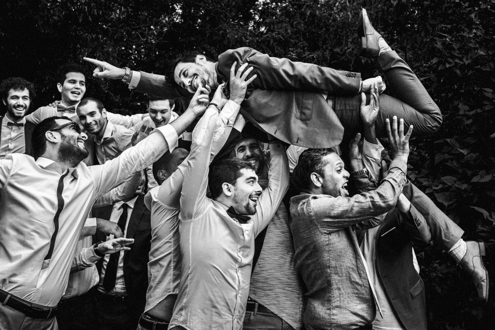 les témoins portent le marié au Moulin du XII par Photo des mains des mariés pendant la cérémonie laïque . Ernestine et sa famille photographe de mariage à l'approche reportage