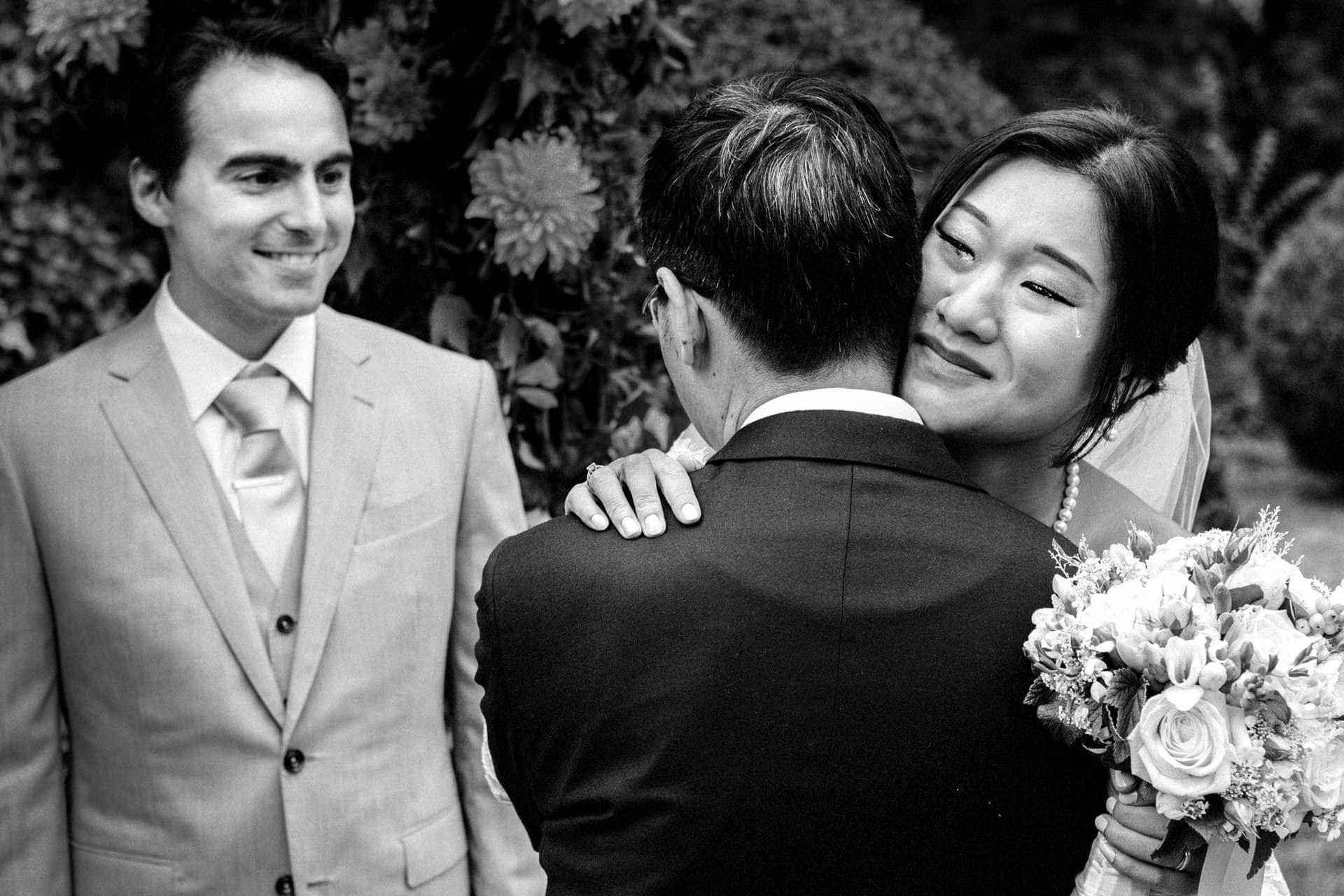 la mariée embrasse son père au chateau de Méridon par Photo des mains des mariés pendant la cérémonie laïque . Ernestine et sa famille photographe de mariage à l'approche reportage